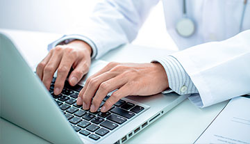 Stock image of doctor's hands on laptop.